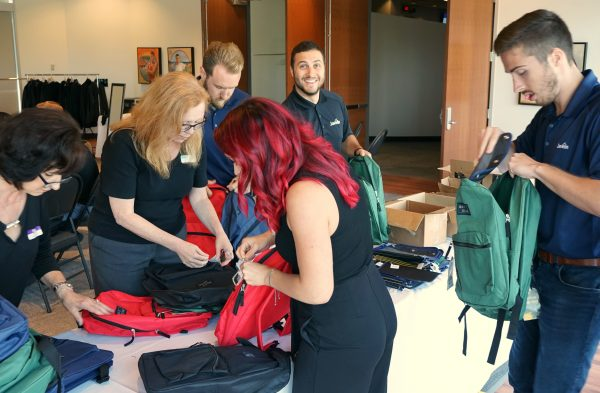 Employees pack school supplies into backpacks for Back to School 2019