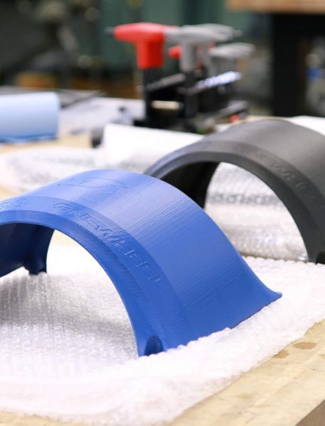 3D printed fender prototypes made from ASA (blue) and FDM Nylon 12CF (black).
