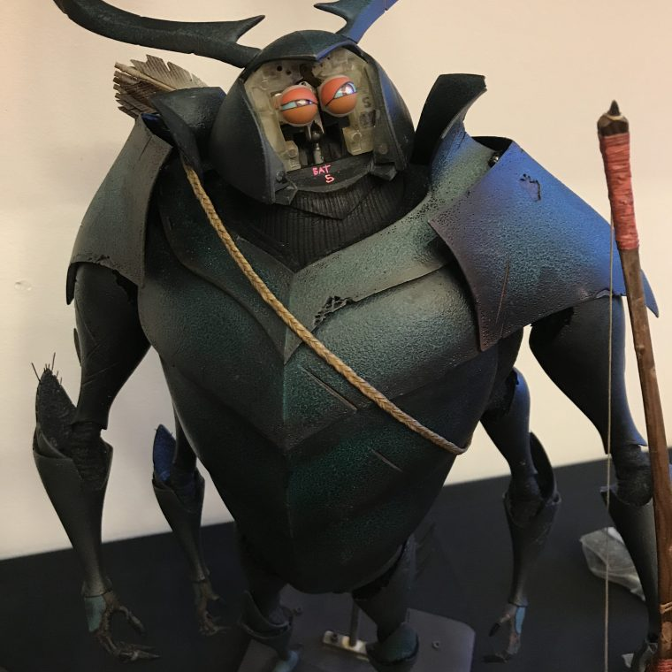 A Beetle puppet displaying the way that the Laika team were able to change the facial characteristics of the puppet for the film Kubo and the Two Strings in high resolution with realism and consistency by utilizing multi-material 3D printed facial parts.